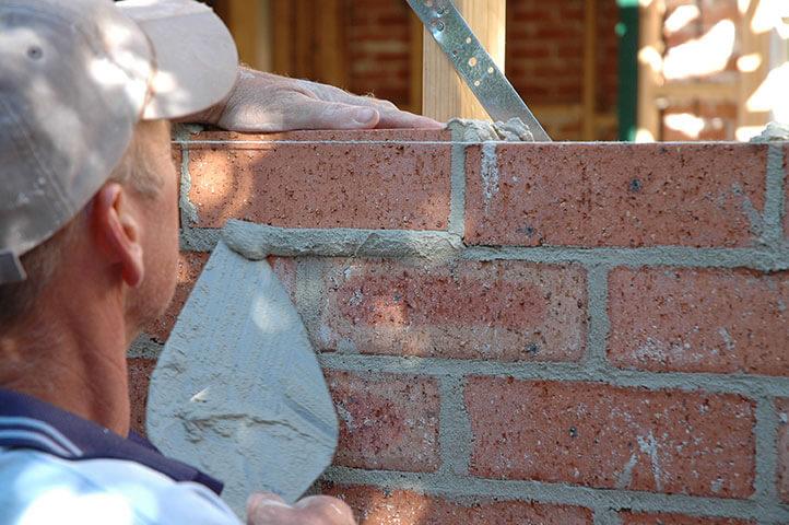 Maçonnerie - Maçon qui fait la pose de brique